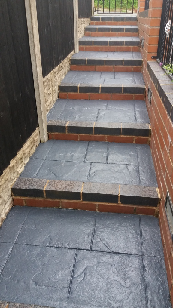 step after they were cleaned and coated , shiny grey steps dark grey edges brick wall to the right
